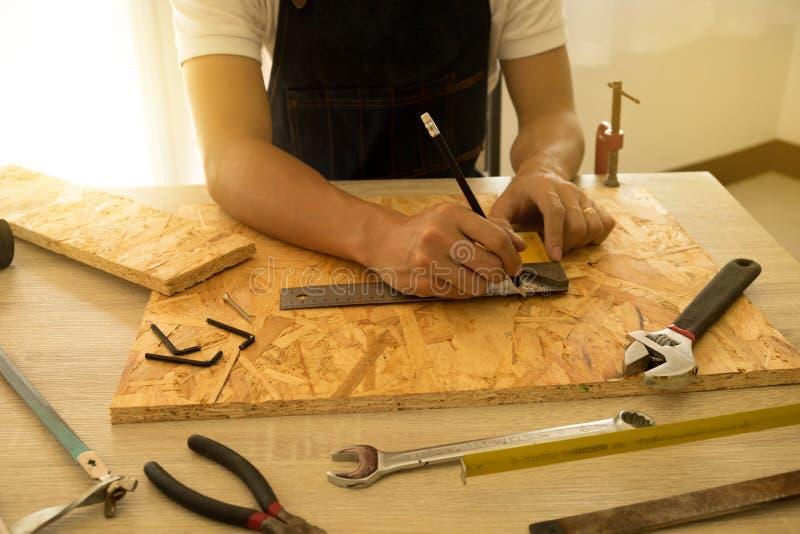 Close-up van mannelijke timmermanshanden die teken trekken op houten bevloering stock foto's
