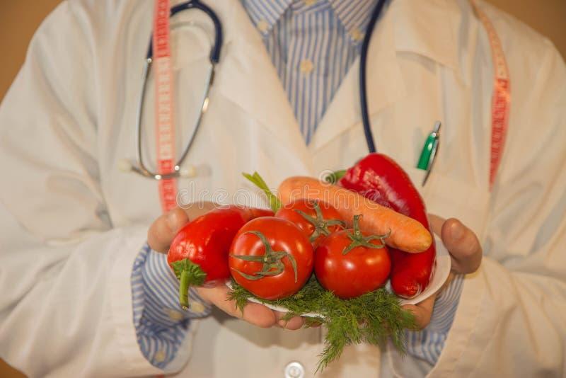 Close-up van mannelijke voedingsdeskundigehanden die groenten met band meten Mensendiëtist die low-calorie voedsel voorschrijven  royalty-vrije stock afbeelding