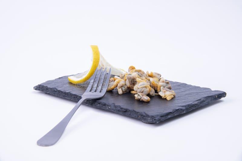 Close-up van mariene voorgerechten - de Smakelijke kokkels en de citroen dienden op een zwarte rustieke steenraad stock foto's