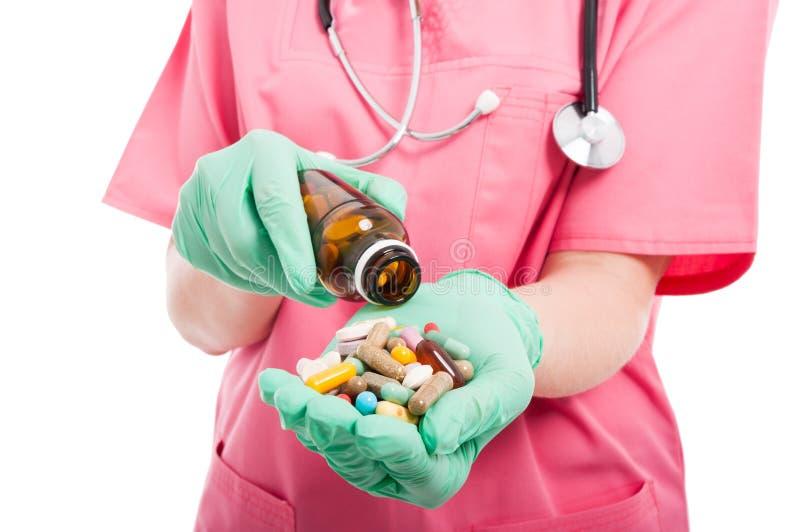 Close-up van medische verpleegster die een fles van pillen morsen royalty-vrije stock afbeeldingen