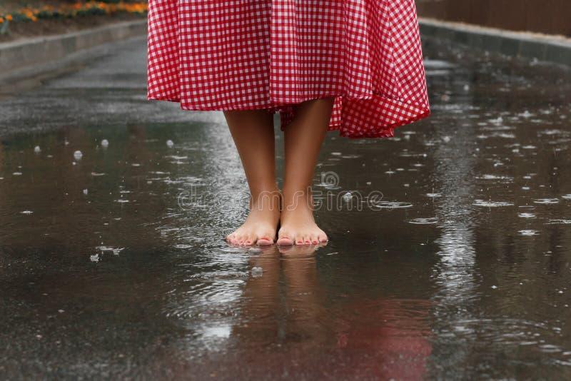 Close-up van meisjes` s voeten die in een vulklei na een de zomerregen dansen royalty-vrije stock foto