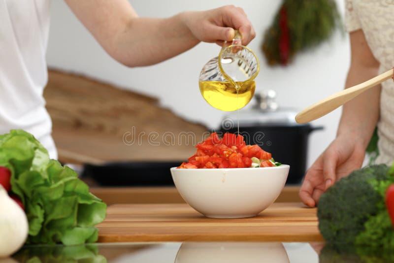 Close-up van Menselijke handen die in keuken koken Moeder en dochter of twee vrouwelijke vrienden die groenten voor verse salade  royalty-vrije stock foto's