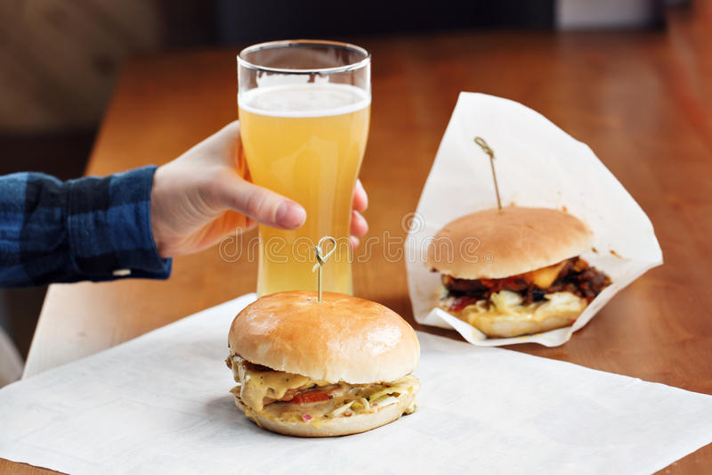 Close-up van mensen` s hand die een glas bier houden Heerlijke goed uitgevoerde die hamburger twee met uien, tomaten, cheddar wor stock foto's