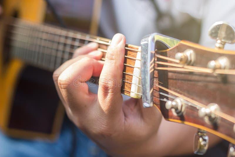 Close-up van mensen` s handen die akoestische gitaar spelen stock afbeeldingen