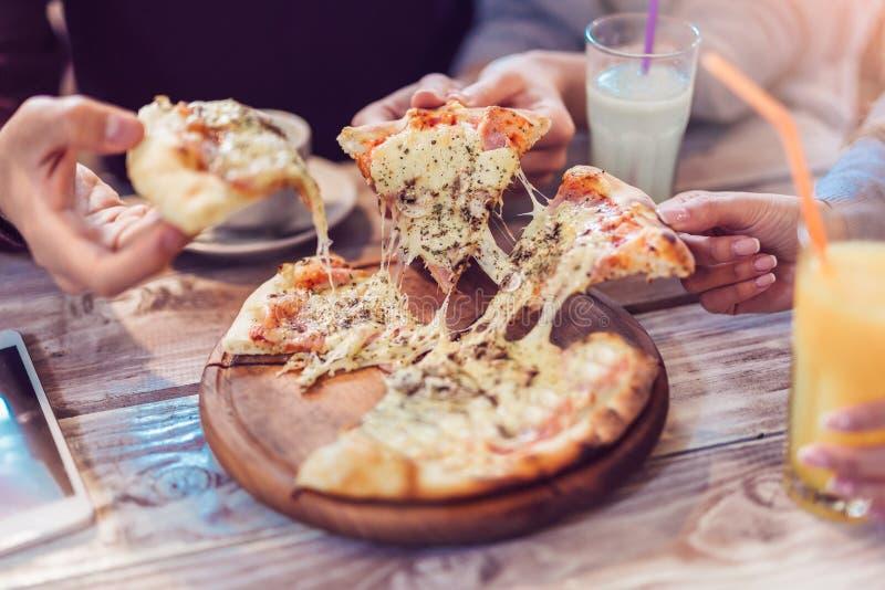 Close-up van Mensenhanden die Plakken van Pizza nemen stock afbeelding