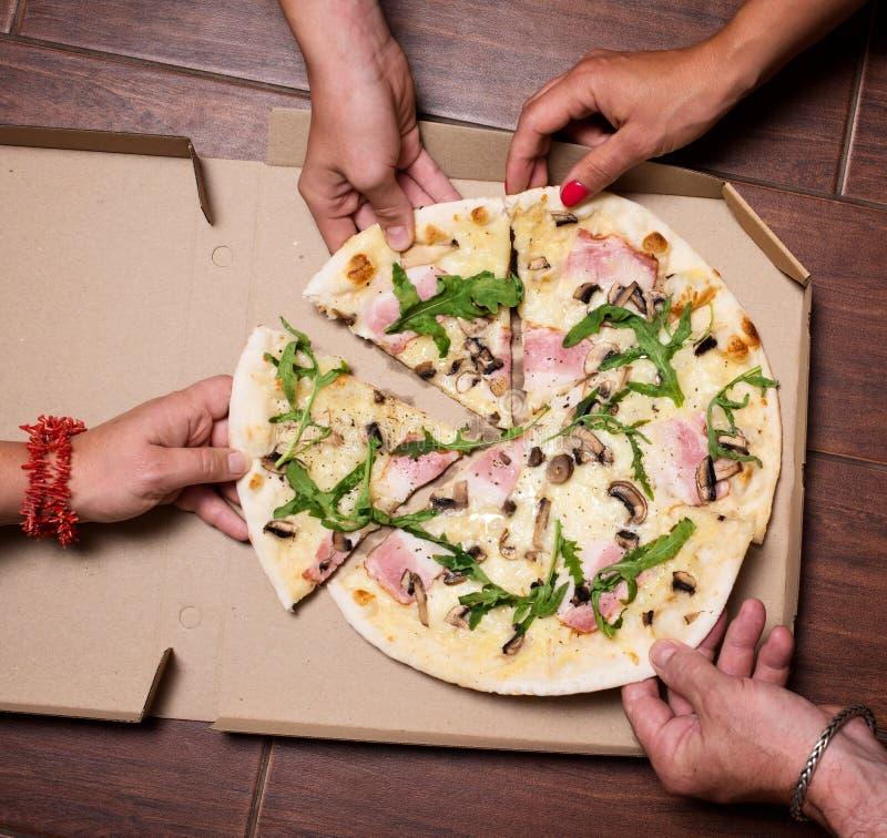 Close-up van Mensenhanden die Plakken van Pizza nemen Groep Vrienden die Pizza samen delen Het eten van voedsel Snel Voedsel, Vri stock fotografie