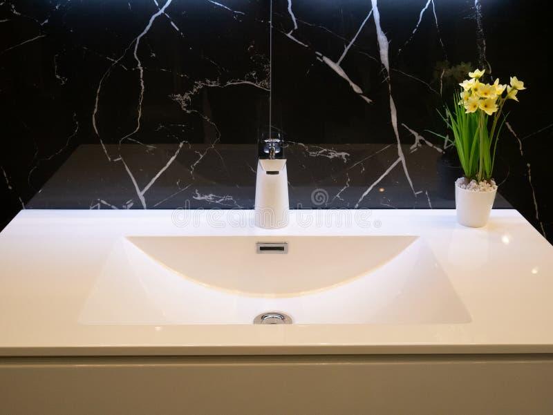 Close-up van moderne badkamers zuivere witte wasbak met chroomtapkraan en vaas met bloemen muur van zwart marmer wordt gemaakt da royalty-vrije stock afbeeldingen