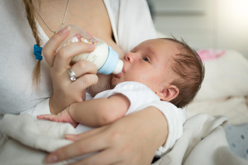 Close-up van moeder die pasgeboren baby van fles voeden royalty-vrije stock fotografie