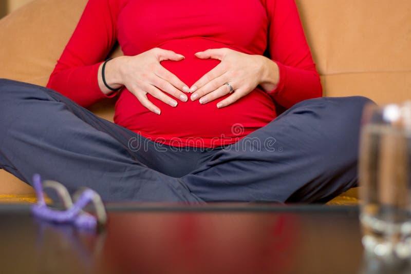 Close-up van moederhanden die haar zwangere buik strelen stock afbeelding