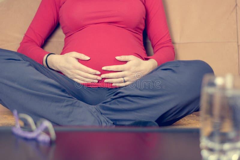 Close-up van moederhanden die haar zwangere buik strelen stock fotografie