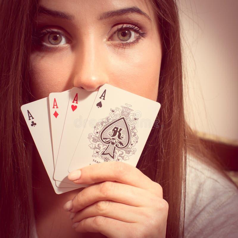 Close-up van mooie donkerbruine jonge vrouwenspeelkaarten die vier azen houden stock afbeeldingen