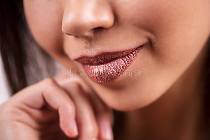 Close-up van mooie glimlachende donker-gevilde vrouwen, macro, detailschot Glanzende bruine lippenstift, lipgloss, schoonheidsmid stock foto