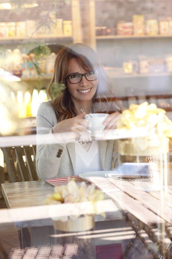 Close-up van mooie rijpe vrouw in koffiewinkel stock afbeeldingen