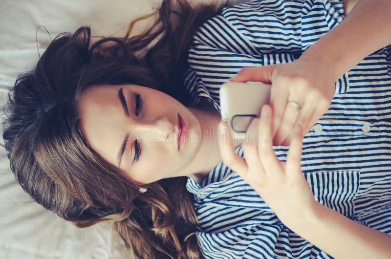 Close-up van mooie tiener die in bed liggen het bekijken haar mobiele telefoon stock foto's