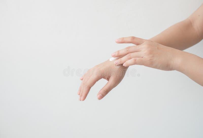 Close-up van mooie vrouwelijke handen die handen houden en een vochtinbrengende crème toepassen De hand die van de schoonheidsvro stock afbeelding