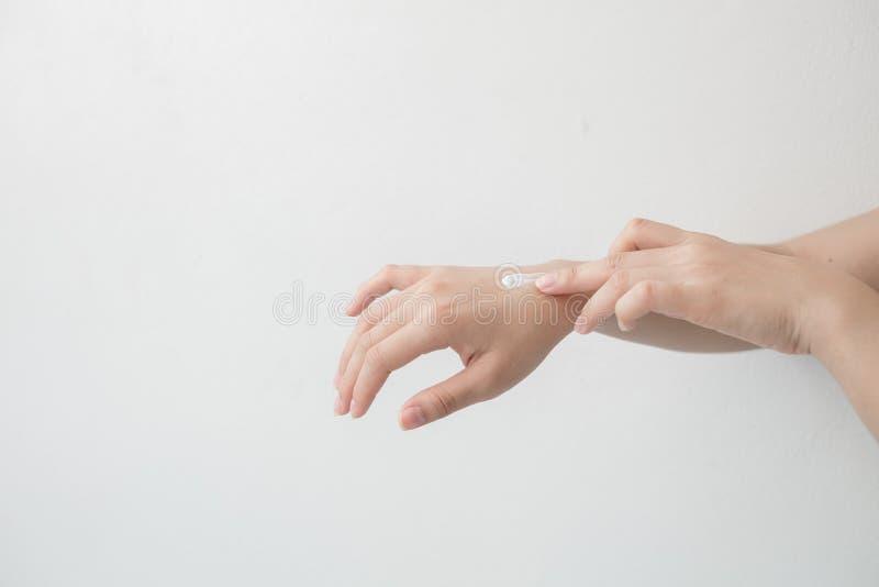 Close-up van mooie vrouwelijke handen die handen houden en een vochtinbrengende crème toepassen De hand die van de schoonheidsvro stock foto