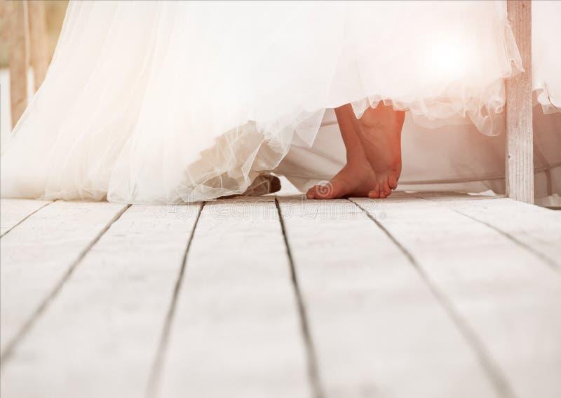 Close-up van naakte voeten van een bruid op een houten oppervlakte Huwelijksbac stock foto