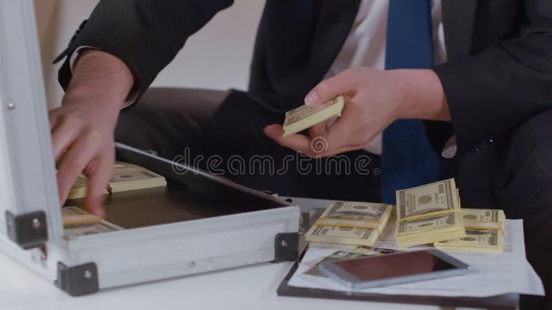 Close-up van ondernemers tellend geld van aktentas, terugslag in zaken royalty-vrije stock afbeeldingen