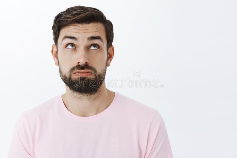 Close-up van ongelukkig, vermoeid en verstoord aantrekkelijk jong gebaard mannetje die met baard wordt wenkbrauwen in wanhoop het stock fotografie