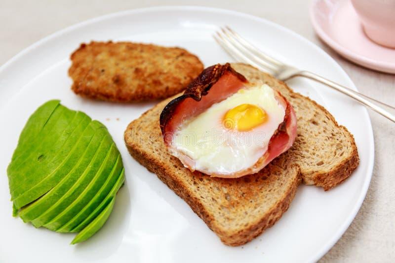 Close-up van ontbijt met ei, bacon en toost, avocado royalty-vrije stock afbeeldingen
