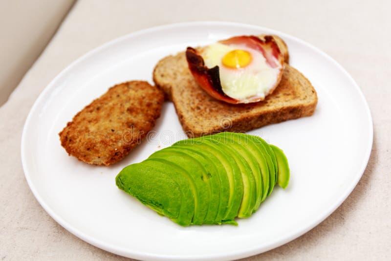 Close-up van ontbijt met ei, bacon en toost, avocado stock afbeelding