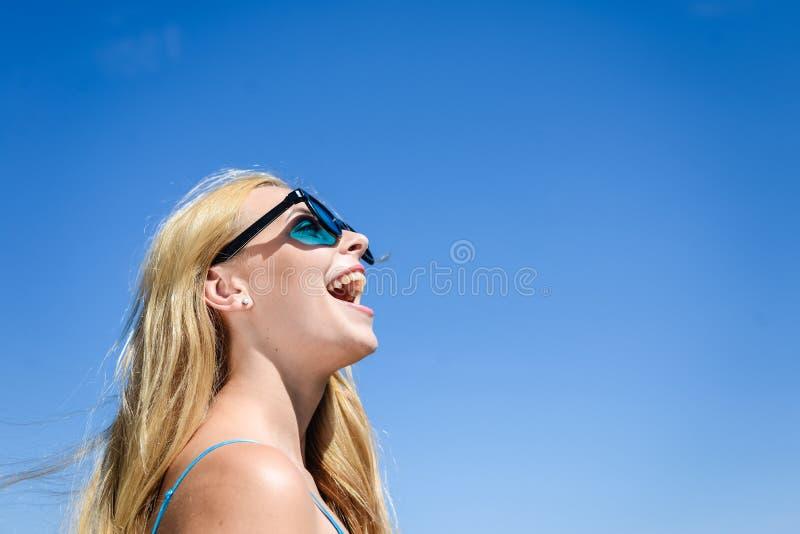 Close-up van opgetogen gelukkige jonge blonde mooie dame in zonnebril over blauwe hemel op de zomerdag in openlucht royalty-vrije stock fotografie