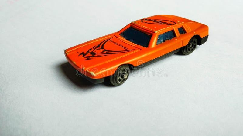 Close-up van oranje stuk speelgoed auto voor kinderen op wit geïsoleerde achtergrond stock afbeelding