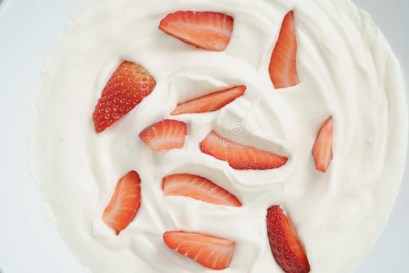 Close-up van organische yoghurt met verse gesneden aardbeien stock foto's