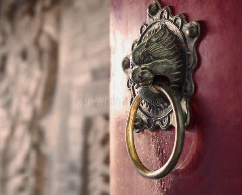 Close-up van overladen gouden deurkloppers op rode deur stock foto's
