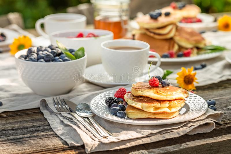 Close-up van pannekoeken met frambozen, bosbessen en honing stock foto's
