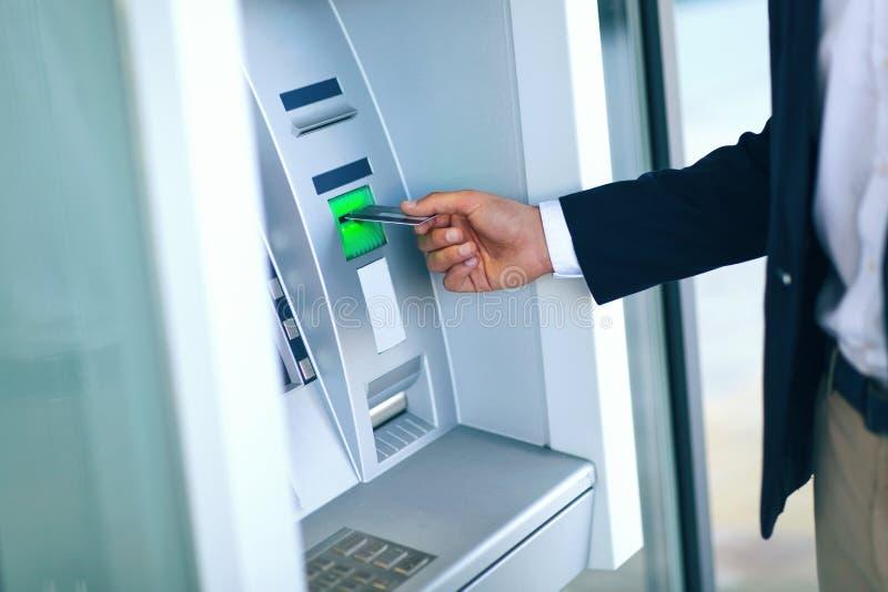 Close-up van Person Using Credit Card To die Geld terugtrekken stock foto's