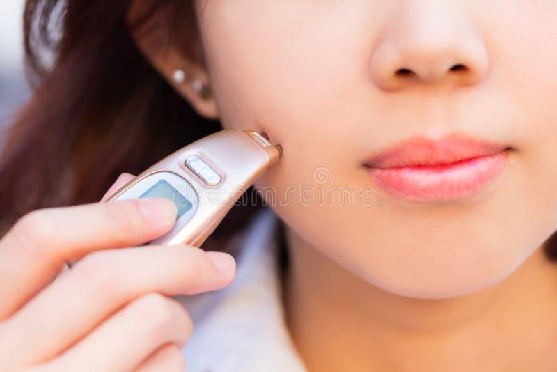 Close-up van persoonshand die huidgezicht met Dermatoscope controleren royalty-vrije stock afbeeldingen