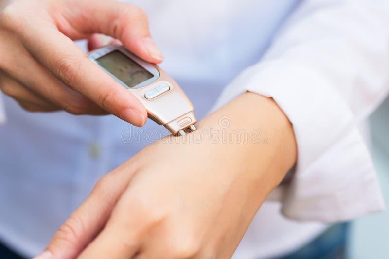 Close-up van persoonshand die huidhand met Dermatoscope controleren stock foto's