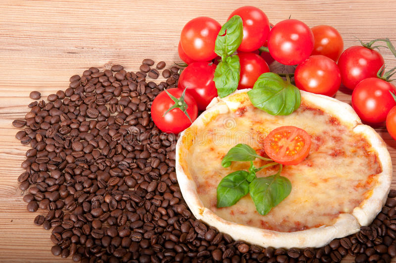 Close-up van pizza met koffiebonen, tomaten, kaas en basilicum op houten achtergrond royalty-vrije stock fotografie