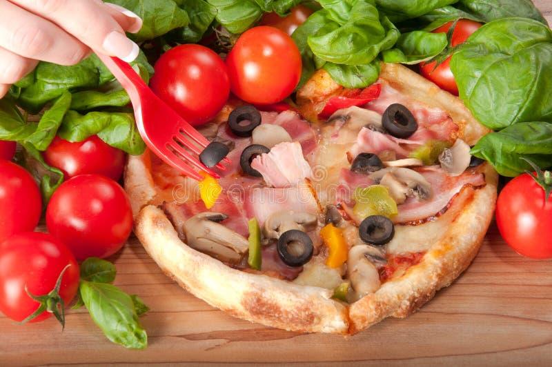 Close-up van pizza met rood vork, tomaten, kaas en basilicum op houten achtergrond royalty-vrije stock foto