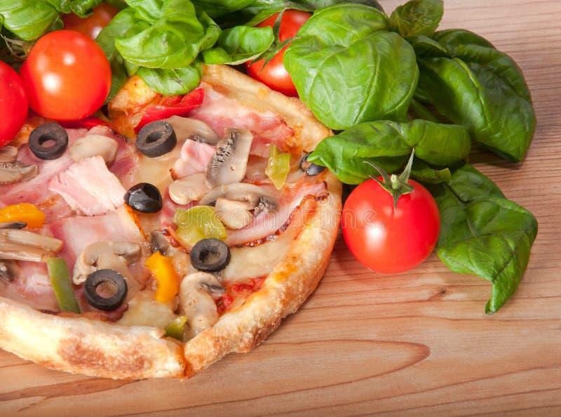 Close-up van pizza met tomaten, kaas en basilicum op houten achtergrond stock afbeelding