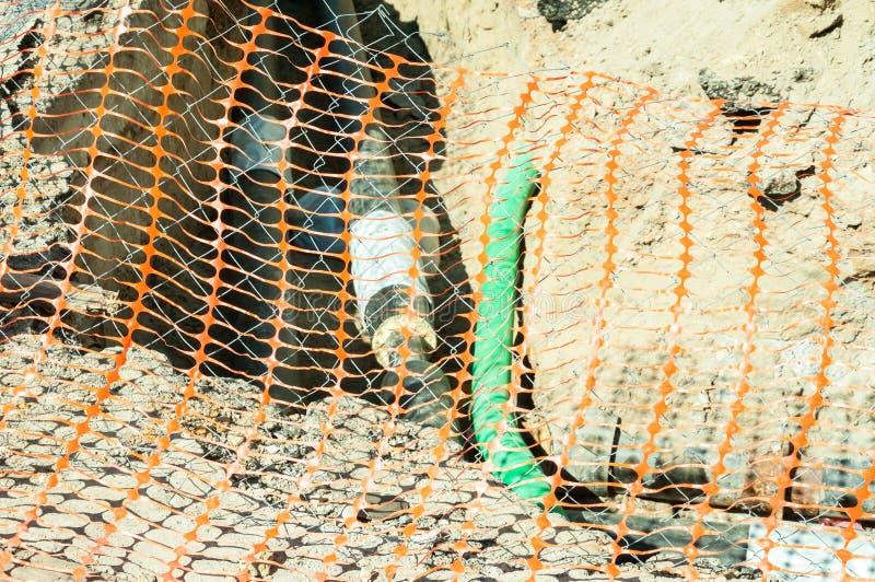 Close-up van plastic oranje die veiligheidsnet als veiligheidsomheining op de straat plaats van de het systeemuitgraving van de s stock afbeelding