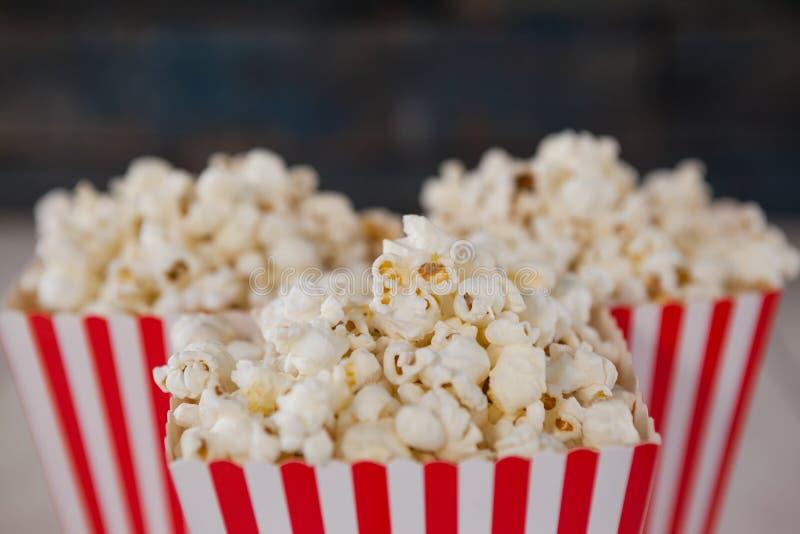 Close-up van popcorn op houten lijst wordt geschikt die stock foto's