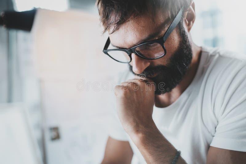 Close-up van portret van aantrekkelijke ontwerper die oogglazen dragen en bij de moderne lightful bureauzolder werken horizontaal stock afbeelding