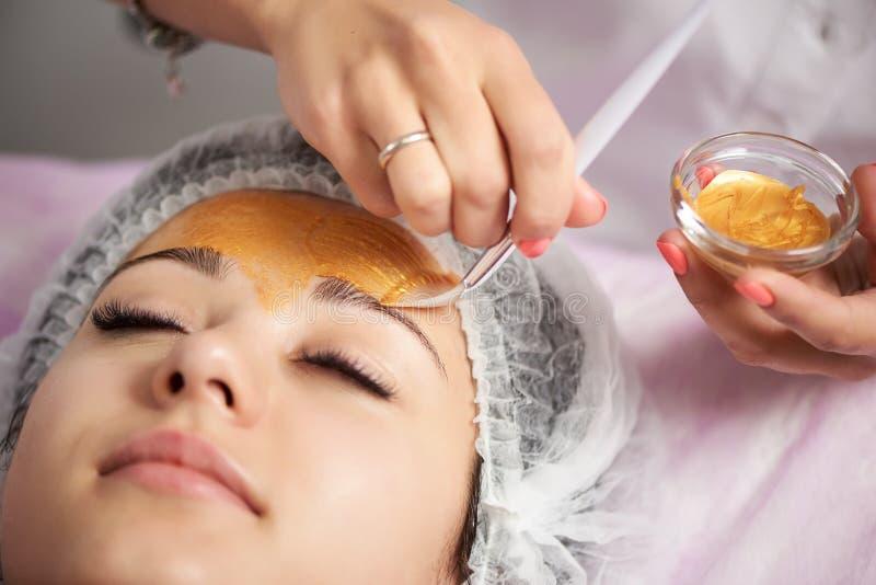 Close-up van portret die van mooi meisje gouden gezichtsmasker toepassen stock foto