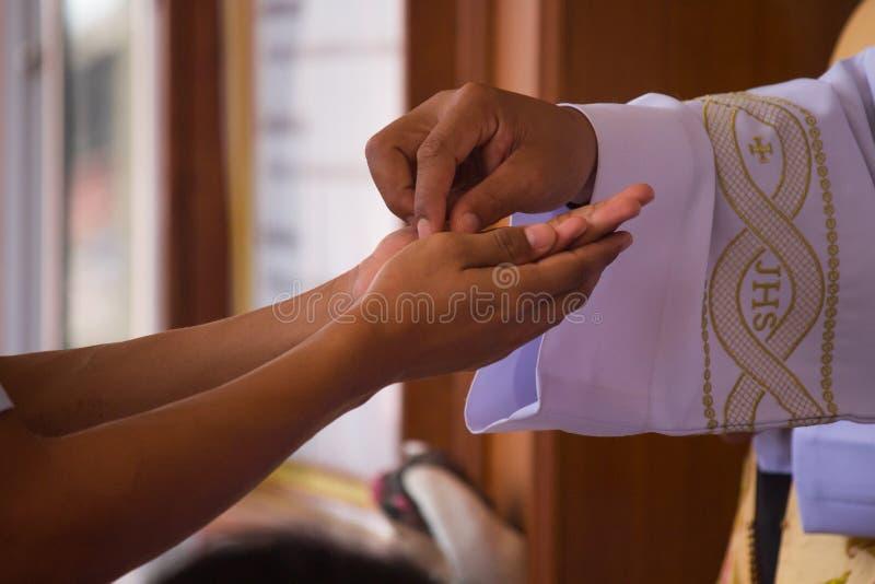 Close-up van priester met kerkgemeenschap in de hand stock afbeeldingen