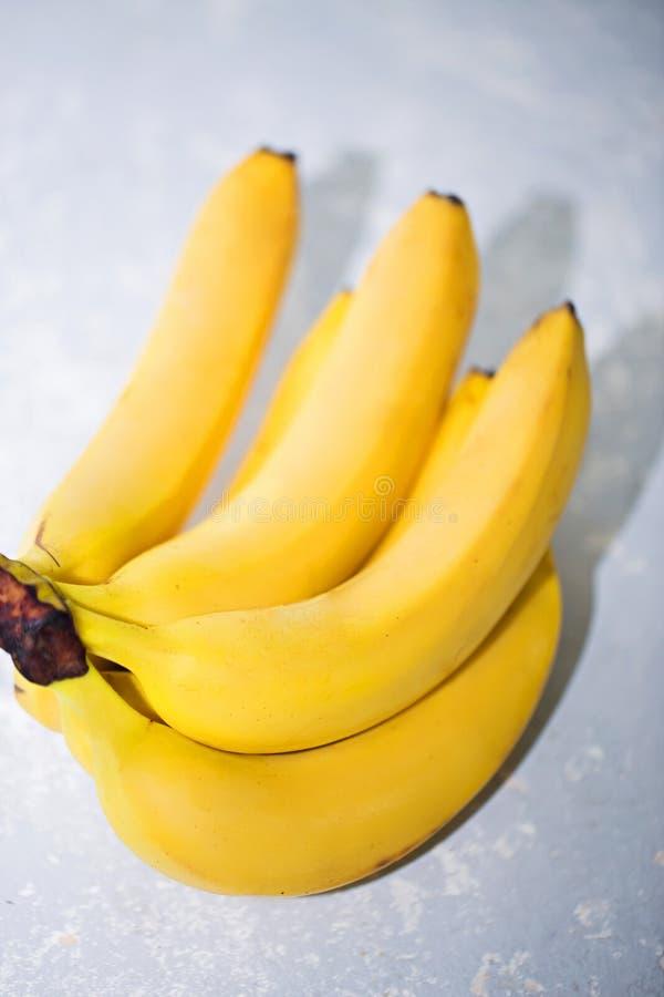 Close-up van rijpe gele bananen op grijze achtergrond Fruit, gezond voedsel, marktconcept royalty-vrije stock foto