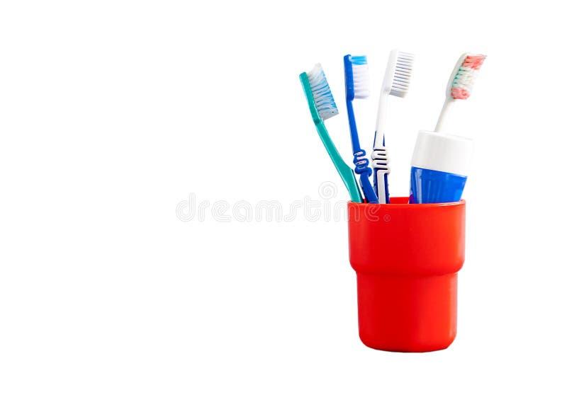 Close-up van rode en blauwe plastic tandenborstels in een rode mok op een wit Tandconcept als achtergrond royalty-vrije stock afbeeldingen