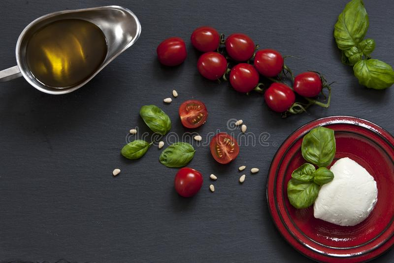 Close-up van rode kersentomaten met witte mozarellakaas, olijfolie en groene bladeren van basilicum op zwarte achtergrond royalty-vrije stock foto