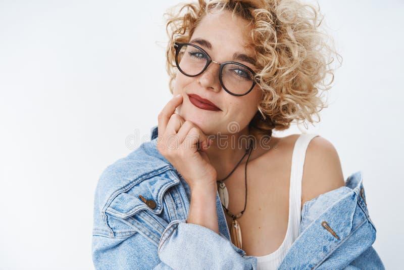 Close-up van romantisch en zelf-verzekerd modern meisje met het blonde flirty die en teder kapsel en glazen glimlachen wordt gesc stock foto's