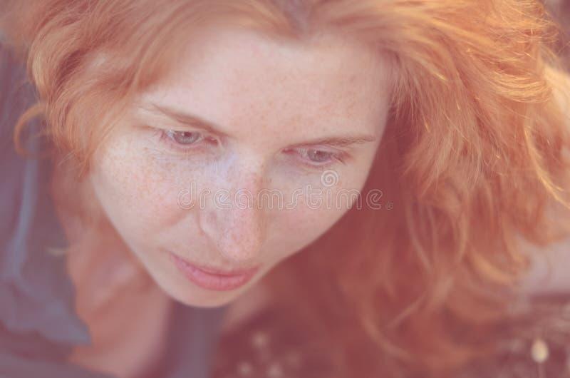 Close-up van roodharig meisje met sproeten het kijken stock afbeeldingen