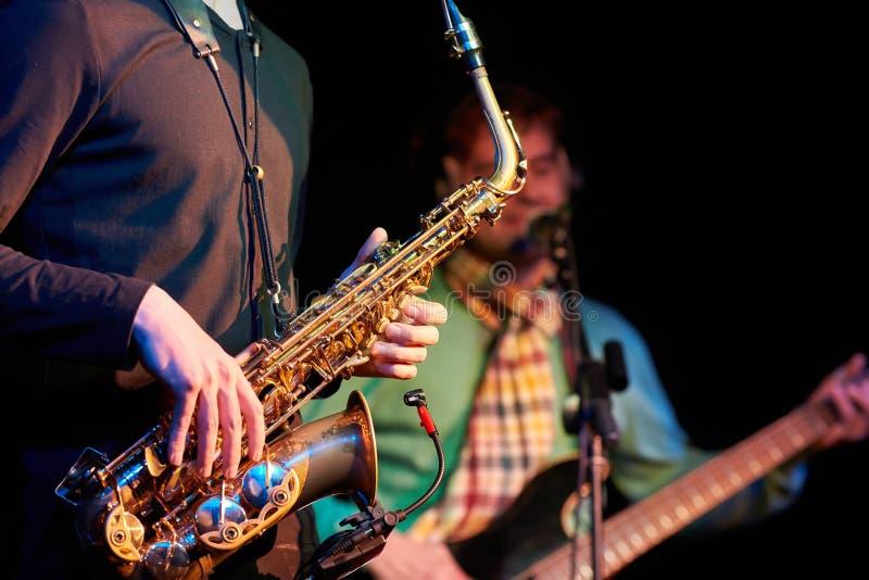Close-up van saxofonist en gitarist het spelen saxofoon en een gui stock afbeelding