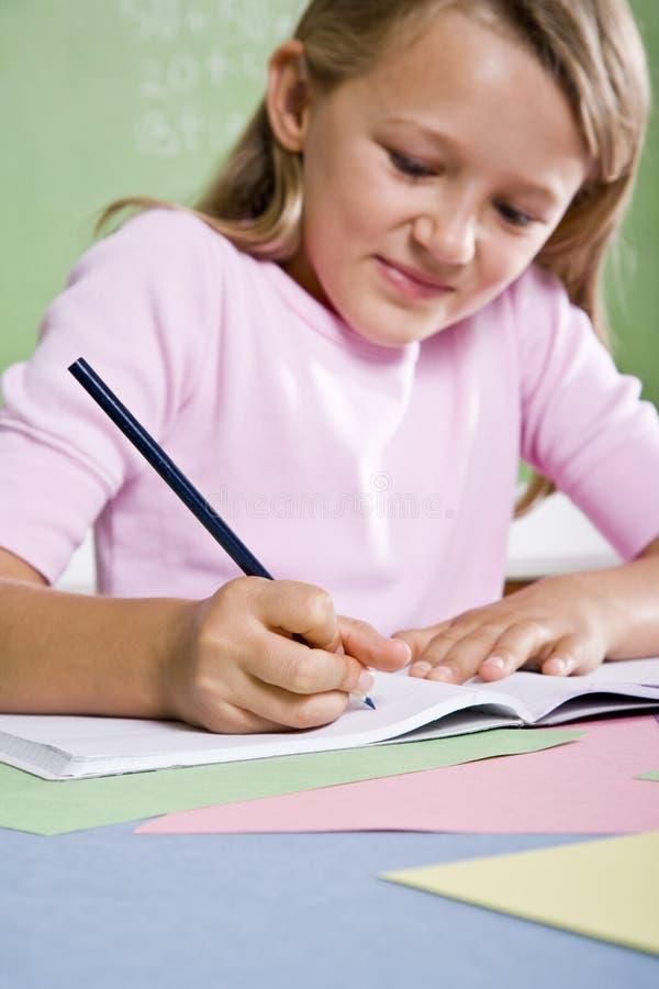 Close-up van schoolmeisje het schrijven in notitieboekje stock afbeelding
