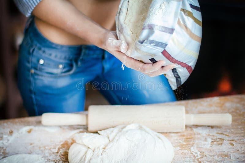 Close-up van sexy meisjesbuik, deeg, bloemzak en deegrol De sexy jonge vrouw bereidt deeg in de keuken voor stock foto's