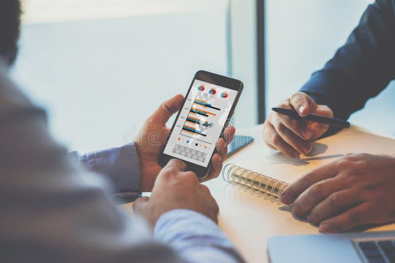 Close-up van smartphone met grafieken, diagrammen en grafieken op het scherm in handen die van zakenman, bij een lijst zitten royalty-vrije stock afbeelding